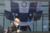 A man walks by an electric monitor promoting the Tokyo 2020 Olympics planned to start in the summer of 2021, in Tokyo, Wednesday, Jan. 27, 2021. (AP Photo/Koji Sasahara)