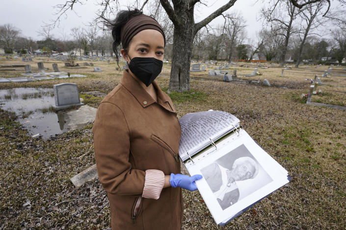 Nadia Orton, a genealogist and family historian in Virginia, opens a binder of research next to the grave of a Civil War era slave at the Lincoln Memorial Cemetery in Portsmouth, Va., Tuesday, March 23, 2021. Orton has worked tracing her own family and others to historically Black cemeteries. (AP Photo/Steve Helber)