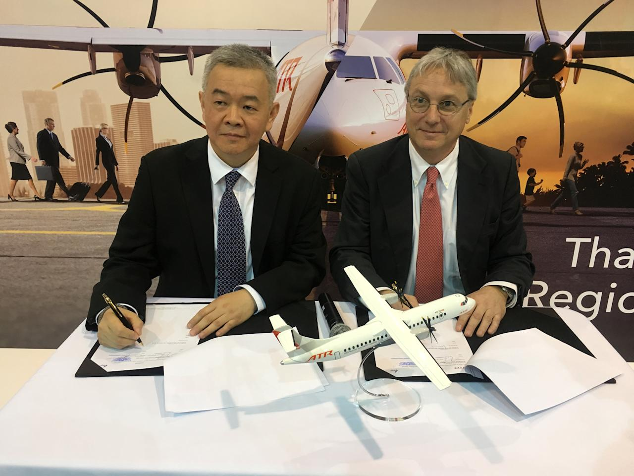 Anawat Leelawatwatana, senior vice-president for finance and accounting at Bangkok Airways, and ATR's Chief Executive Officer Christian Scherer, sign a deal for 4 ATR 72-600s at a ceremony at the Singapore Airshow February 7, 2018.      REUTERS/Brenda Goh