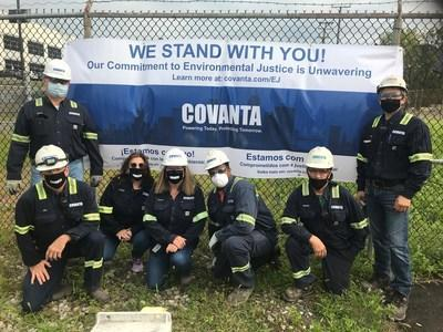 Covanta Essex employees stand outside the Newark, NJ facility with a banner in support of the community and environmental justice