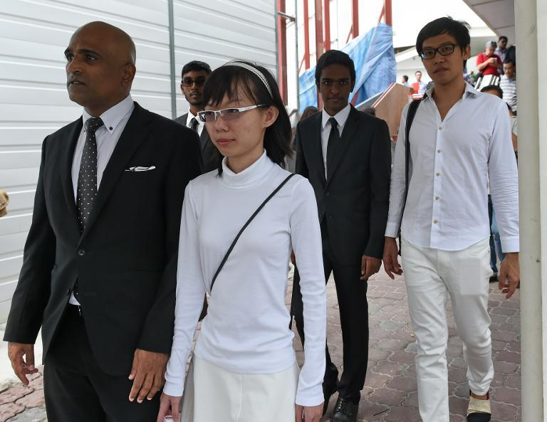 Two Singaporean activists Roy Ngerng (rear R) and Han Hui Hui (front R) with their lawyer M. Ravi (front L) leave the State Court building in Singapore on October 27, 2014
