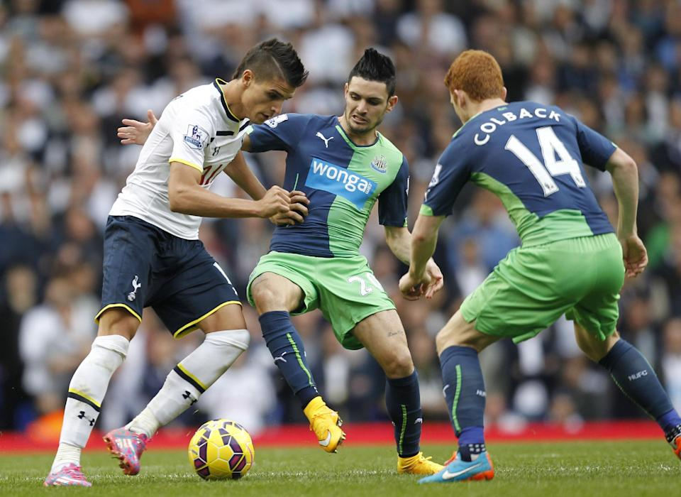 Tottenham Hotspur's Erik Lamela (L) fights for the ball with Newcastle United's Remy Cabella and Jack Colback (R) during their English Premier League match at White Hart Lane in north London, on October 26, 2014 (AFP Photo/Ian Kington)