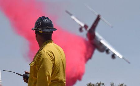 A firefighter watches as a BAe-146 makes a phos-chek drop along the western flank of the Fire near W Camino Cielo while fighting the Whittier Fire near Santa Barbara, California, U.S. July 15, 2017. Mike Eliason/Santa Barbara County Fire Department/Handout via REUTERS