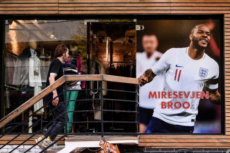 "a clothing store in Pristina put up a giant banner with a picture of Raheem Sterling, the Manchester City star, with an inscription ""Miresevjen broo (Welcome bro)"" (AFP Photo/Armend NIMANI)"
