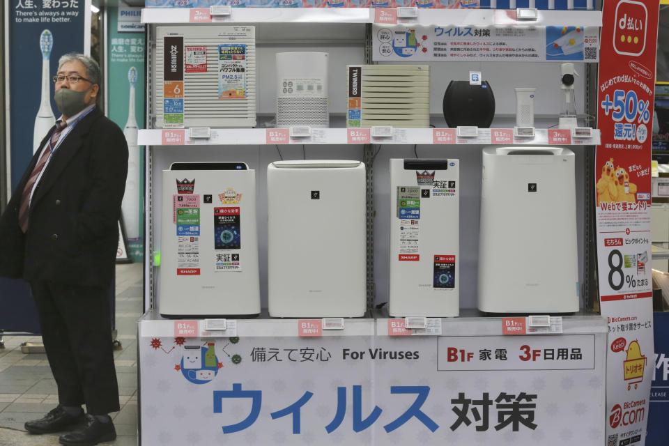 "A man wearing a face mask to protest against the coronavirus stands beside a display of air cleaners at an electronics retailer in Tokyo, Tuesday, Jan. 12, 2021. The Tokyo area has been under a state of emergency since Friday to try to stop the spread of the virus. The banner at bottom reads: ""Antivirus."" (AP Photo/Koji Sasahara)"