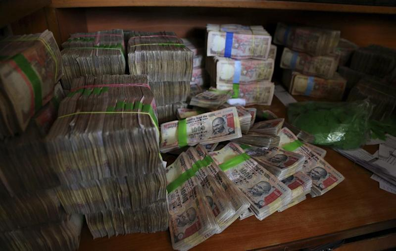 FILE - In this Nov. 10, 2016, file photo, discontinued Indian currency notes of 1,000 denomination are seen after they were exchanged at a bank in Bangalore, India, in a government effort to crack down on corruption by banning high-denomination currency notes. A survey by the anti-graft group Transparency International shows that bribery and other forms of corruption are hindering poverty alleviation and hurting public health by channeling resources away from those who need them. The survey, released Tuesday, March 7, 2017, estimated that more than 900 million people in the region had paid bribes in the past year to obtain basic public services like schooling and health care. (AP Photo/Aijaz Rahi, File)