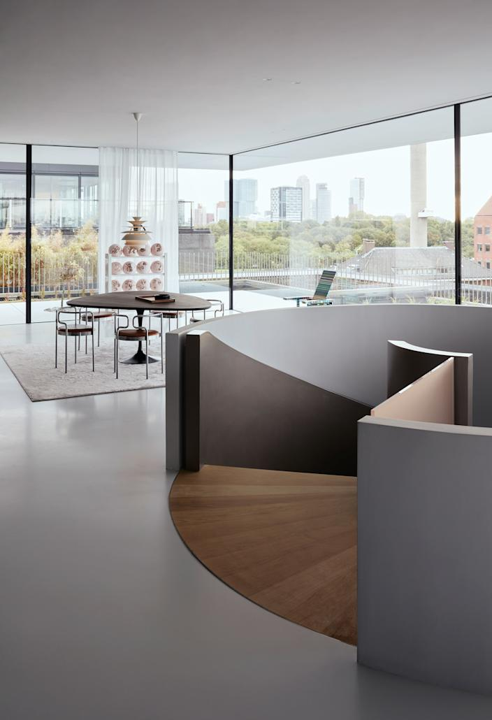 """<div class=""""caption""""> The two floors are linked by a generous, signature spiral staircase, by which visitors arrive in the living room, surrounded by glass and jaw-dropping views of the River Maas and the city skyline. The floor is a light gray resin and the basketball artwork in the background is by Daniel Arsham. </div>"""