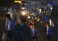 A family wearing face masks as a precaution against the coronavirus walk carrying their luggage through a street at night in Hyderabad, India, Wednesday, Feb. 3, 2021. (AP Photo/Mahesh Kumar A.)