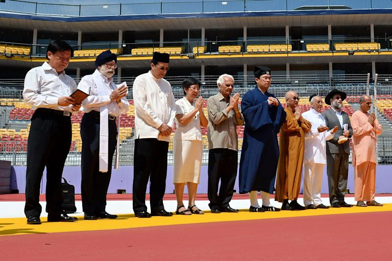 Representatives from Singapore's various religious groups saying a prayer ahead of the Formula One night race in September 2013. (PHOTO: AFP)