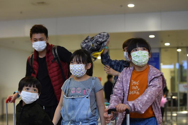 This picture taken on February 2, 2020 shows travellers wearing protective facemasks at Noi Bai international airport in Hanoi. - Vietnam suspended mainland China flights over virus fears as it spread to two dozen nations and killed 259 people in China where it originated in the city of Wuhan. (Photo by Nhac NGUYEN / AFP) (Photo by NHAC NGUYEN/AFP via Getty Images)