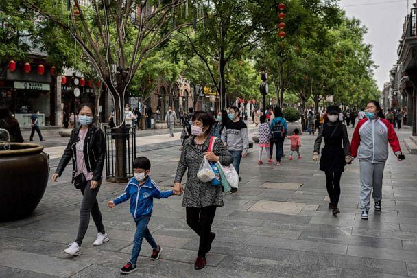PHOTO: People wearing face masks as a preventive measure against the novel coronavirus walk on a street in Beijing, China, on May 4, 2020. (Nicolas Asfouri/AFP via Getty Images)