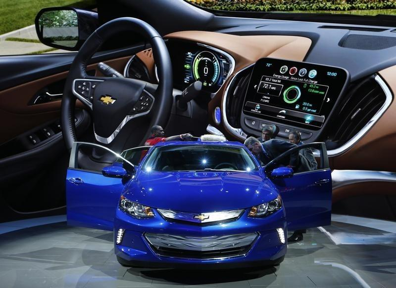 A 2016 Chevrolet Volt hybrid is displayed in front of a large illustration of its dashboard during the second press day of the North American International Auto Show in Detroit