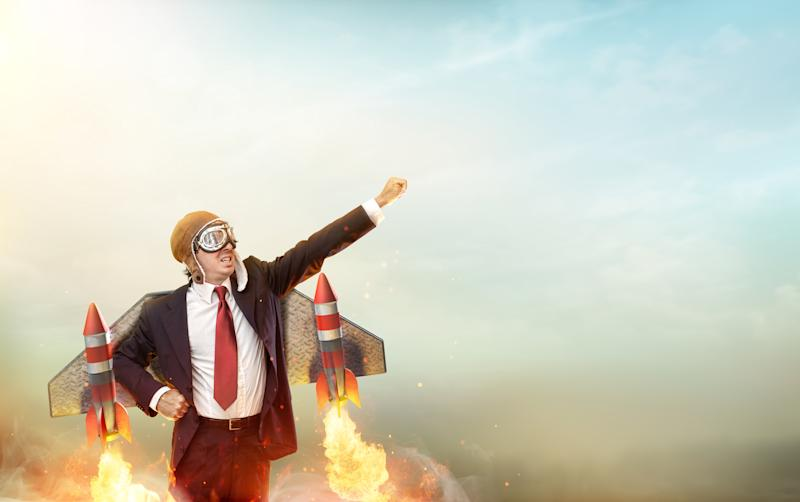 A man in a suit soaring into the sky using a jet pack.