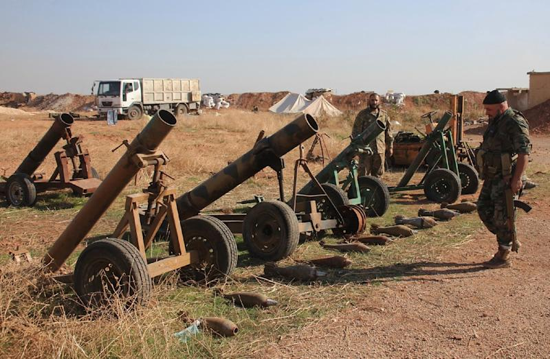 Syrian pro-government forces inspect weapons reportedly left by Islamic State group fighters at a train station in the area of Arkile near the airport of Kweyris, in the northern Syrian province of Aleppo, on November 20, 2015 (AFP Photo/George Ourfalian)