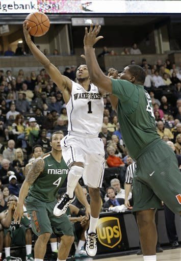 Wake Forest's Madison Jones (1) drives past Miami's Reggie Johnson (42) and Trey McKinney Jones (4) during the first half of an NCAA college basketball game in Winston-Salem, N.C., Saturday, Feb. 23, 2013. (AP Photo/Chuck Burton)