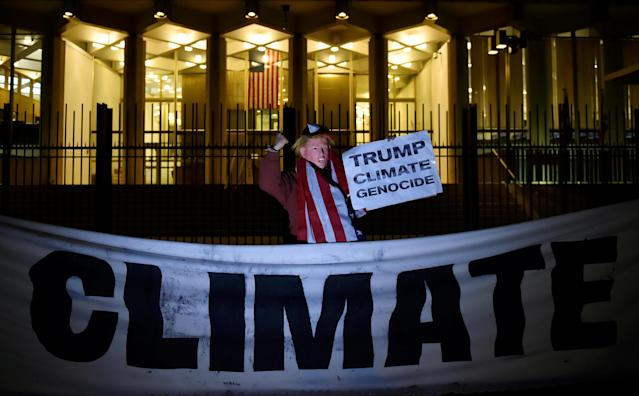 A man wearing a mask depicting Donald Trump protests during a demonstration against climate change outside of the U.S. Embassy in London, Britain, 18 November, 2016. (REUTERS/Hannah McKay)