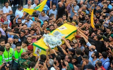 Members of Hizbollah movement carry the coffin of the fellow comrade, who was killed in Israeli strikes in Syria - Credit: AFP