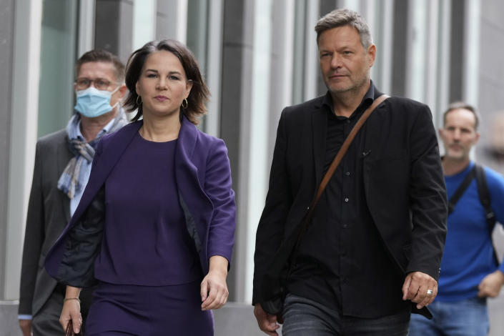 Co-chairwoman of the Greens and candidate for chancellor Annalena Baerbock, left, and co-party leader of the Greens Robert Habeck arrive for a press conference in Berlin, Germany, Monday, Sept. 27, 2021. Following Sunday's election leaders of the German parties were meeting Monday to digest a result that saw Merkel's Union bloc slump to its worst-ever result in a national election and appeared to put the keys to power in the hands of two opposition parties. Both Social Democrat Olaf Scholz and Armin Laschet, the candidate of Merkel's party, laid a claim to leading the next government. (AP Photo/Matthias Schrader)