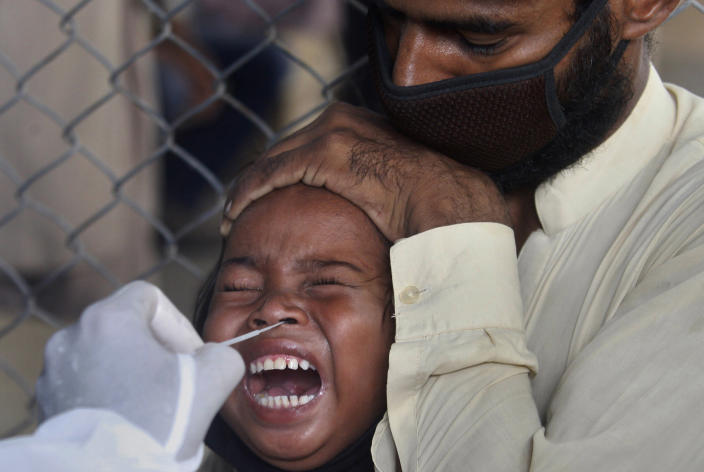 Image: A girl reacts while getting a nasal swab sample at a testing and screening facility for the new coronavirus in a hospital in Karachi, Pakistan (Fareed Khan / AP)