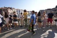 A street vendor sells roses as visitors stand on the Rialto bridge, in Venice, Italy, Thursday, June 17, 2021. After a 15-month pause in mass international travel, Venetians are contemplating how to welcome visitors back to the picture-postcard canals and Byzantine backdrops without suffering the indignities of crowds clogging its narrow alleyways, day-trippers perched on stoops to imbibe a panino and hordes of selfie-takers straining for a spot on the Rialto Bridge or in front of St. Mark's Basilica. (AP Photo/Luca Bruno)