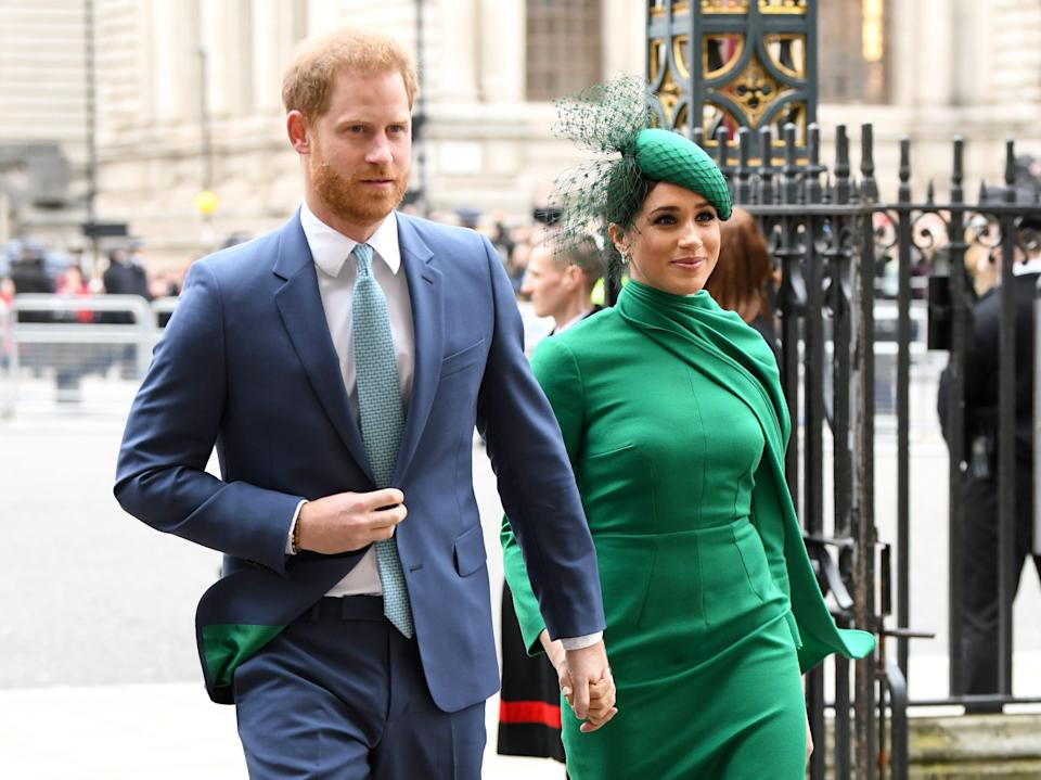 Prince Harry and Meghan Markle in March 2020. Markle wears a green dress, and Harry wears a blue suit with green lining.