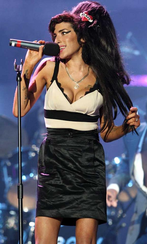 "Amy Winehouse returned to the stage Friday night, where she sang for Nelson Mandela's 90th birthday concert. It was her first public appearance and performance since last week's hospitalization and reports from her father that the British singer had ""traces"" of emphysema. Dave Hogan/<a href=""http://www.gettyimages.com/"" target=""new"">GettyImages.com</a> - June 27, 2008"