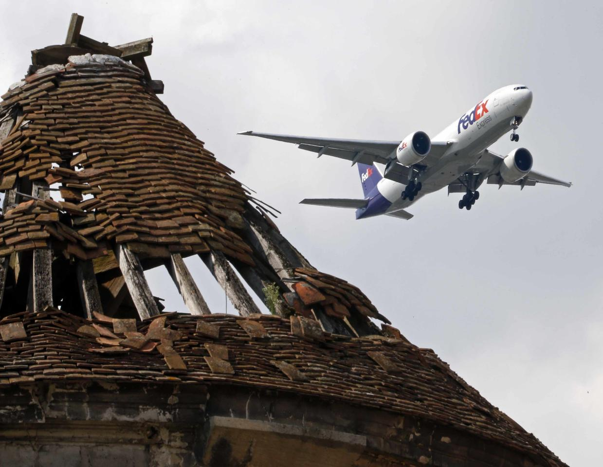 A FedEx plane flies over a former pigeon house, in Goussainville-Vieux Pays, 20 kms (12 miles) north of Paris, August 28, 2013. In 1972 the farming village of 144 homes found itself under the direct flight path of Roissy's Charles de Gaulle Airport when it opened. Residents started to abandon their homes, unable to endure the constant noise of the passenger planes flying overhead. Nowadays, only few families remain living in what has become almost a ghost village. Picture taken August 28, 2013. REUTERS/Charles Platiau (FRANCE - Tags: SOCIETY TRANSPORT)