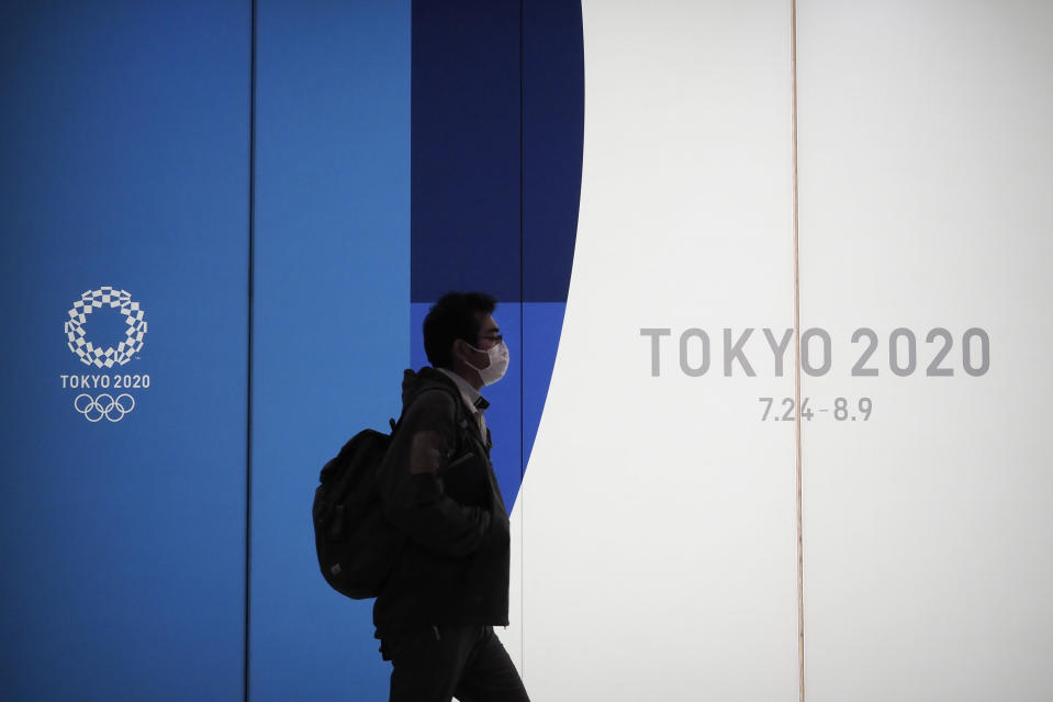 A man walks past a large display promoting the Tokyo 2020 Olympics in Tokyo, Friday, March 13, 2020. U.S. President Donald Trump's suggestion to postpone the Tokyo Olympics for a year because of the spreading coronavirus was immediately shot down by Japan's Olympic minister. For most people, the new coronavirus causes only mild or moderate symptoms. For some it can cause more severe illness. (AP Photo/Jae C. Hong)