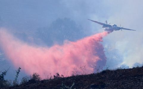 <span>A plane dumps flame retardant on a fast moving fire in Bonsall, California</span> <span>Credit: Reuters </span>