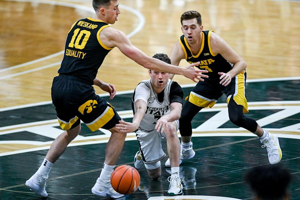 Michigan State's Foster Loyer, center, passes the ball between Iowa's Joe Wieskamp, left, and Jordan Bohannon during the first half on Saturday, Feb. 13, 2021, at the Breslin Center in East Lansing.
