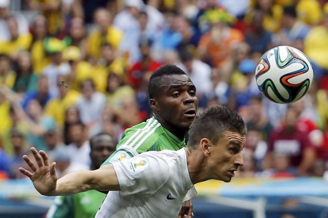 France's Laurent Koscielny reaches for the ball with Nigeria's Kenneth Omeruo (L) during their 2014 World Cup round of 16 game at the Brasilia national stadium in Brasilia June 30, 2014. REUTERS/Siphiwe Sibeko (BRAZIL - Tags: SOCCER SPORT WORLD CUP)