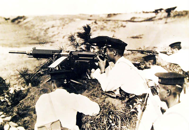FILE PHOTO: Japanese soldiers wearing white uniforms and dress caps pose behind a heavy machine gun on Guadalcanal