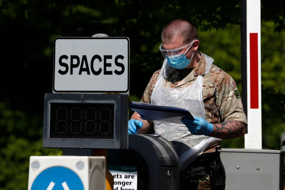 A soldier from the Royal Welsh Regiment consults information on a clipboard at the entrance to a mobile coronavirus COVID-19 testing centre set up in a park and ride site in Salisbury, southern England, on April 26, 2020, during the national lockdown due to the novel coronavirus COVID-19 pandemic. - Britain's health ministry on Saturday said 813 more people had died after testing positive for COVID-19 in hospital, taking the death toll to 20,319. (Photo by Adrian DENNIS / AFP) (Photo by ADRIAN DENNIS/AFP via Getty Images)