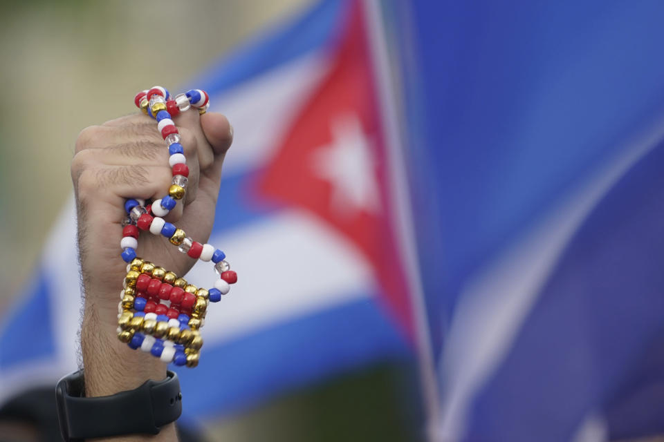 A demonstrator holds up a bead necklace in the colors of the Cuban flag, Wednesday, July 14, 2021, in Miami's Little Havana neighborhood, as people rallied in support of antigovernment demonstrations in Cuba. (AP Photo/Wilfredo Lee)