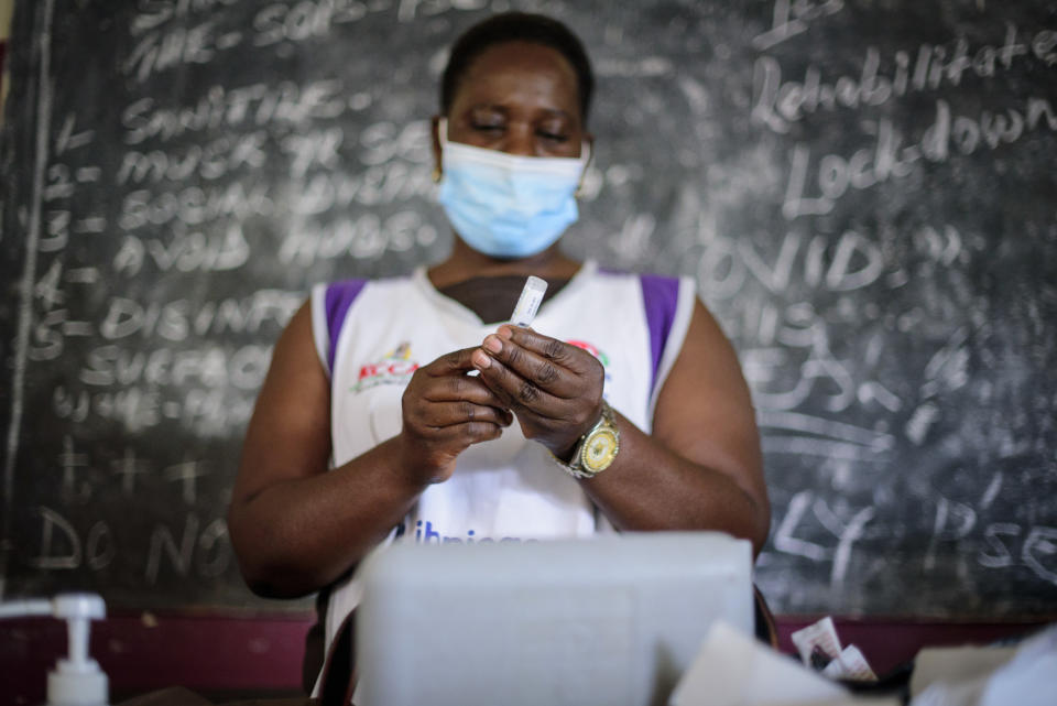 A nurse prepares to administer a coronavirus vaccination at Kisenyi Health Center in downtown Kampala, Uganda Wednesday, Sept. 8, 2021. Uganda is accelerating its vaccination drive in order to administer 128,000 doses that recently arrived and expire at the end of September. (AP Photo/Nicholas Bamulanzeki)