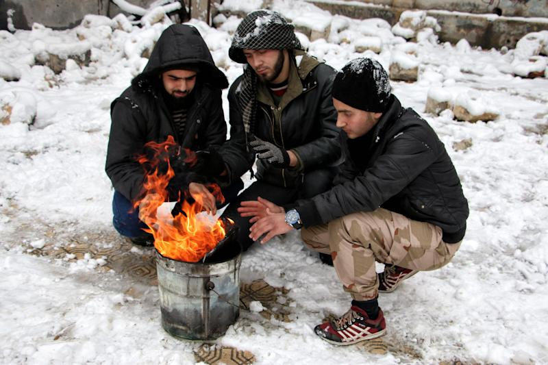 Rebel fighters heat themselves by a fire as snow falls on January 11, 2015 in the rebel-held side of the Syrian northern city of Aleppo (AFP Photo/Karam Al-Masri)