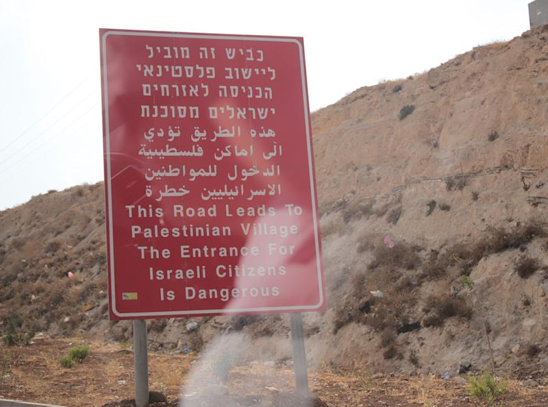 A signed placed outside a Palestinian village in the West Bank warns Israeli citizens to stay out or risk their lives. Photo: Sept. 11, 2019.