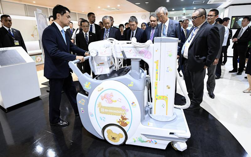 Prime Minister Tun Dr Mahathir Mohamad listens to an explanation of a machine during his visit to Shimadzu Corporation in Kyoto September 6, 2019. — Bernama pic