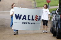 Sisters-in-law Bae Waller, left, and Yonnie Waller, of former Mississippi Supreme Court Chief Justice Bill Waller Jr., a candidate for the GOP nomination for governor, rush to get his campaign sign out of the rain at a north Jackson, Miss., precinct, Tuesday, Aug. 27, 2019. Waller faces Lt. Governor Tate Reeves in the runoff for the Republican Party nomination for governor. (AP Photo/Rogelio V. Solis)