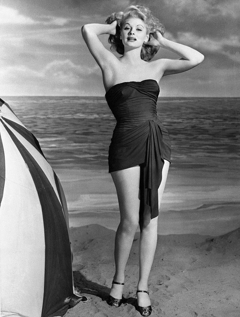 <p>Lucille Ball poses for a glamour shot next to a giant beach umbrella in 1943.</p>