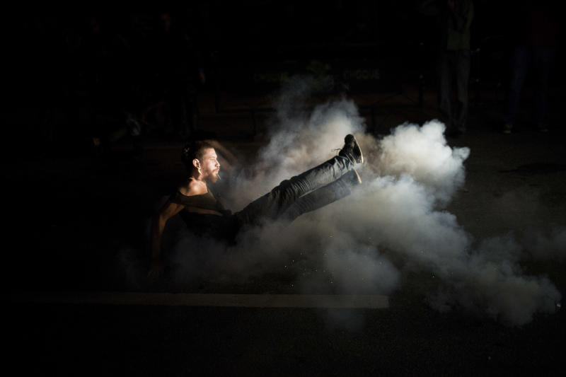 A supporter of the indigenous people who have been occupying the old Indian Museum kicks a can of tear gas in Rio de Janeiro, Friday, March 22, 2013. The clash Friday is a bid to expel the group, some of whom have been squatting in the crumbling complex for years. The Indian museum has been at the center of a drawn-out legal battle between the several dozen Indians who've been living there for years and state and local authorities. Officials initially wanted to raze the complex as part of renovations ahead of Brazil's 2014 World Cup. (AP Photo/Felipe Dana)