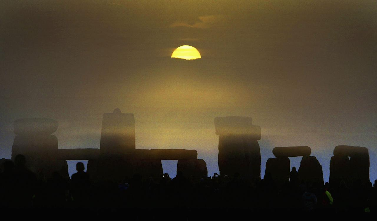 SALISBURY, ENGLAND - JUNE 21: The midsummer sun rises over the megalithic monument of Stonehenge on June 21, 2004. Thousands of people gathered at the ancient site to witness the Summer Solstice on the longest day of the year in the Northern hemisphere. (Photo by Ian Waldie/Getty Images)