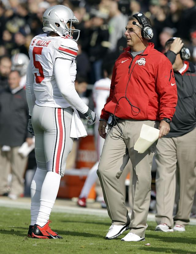 Ohio State quarterback Braxton Miller, left, talks with head coach Urban Meyer during the first half of an NCAA college football game against Purdue in West Lafayette, Ind., Saturday, Nov. 2, 2013. (AP Photo/Michael Conroy)