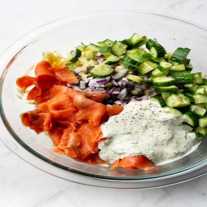 Cucumber, smoked salmon, capers, and yogurt sauce in a bowl.