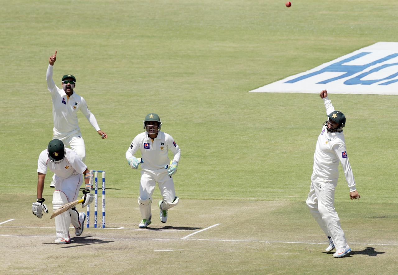 Pakistan fielder Azhar Ali at shortleg (R) throws up the ball in celebration after catching the wicket of Sikanda Raza Butt during the fifth day of the first test match between Pakistan and hosts Zimbabwe at the Harare Sports Club on September 7, 2013.  AFP PHOTO / JEKESAI NJIKIZANA        (Photo credit should read JEKESAI NJIKIZANA/AFP/Getty Images)