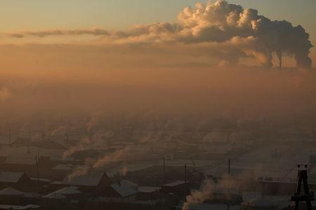 Power plant chimneys stand behind a coal burning neighbourhood covered in a thick haze on the outskirts of Ulaanbaatar, Mongolia January 19, 2017. REUTERS/B. Rentsendorj