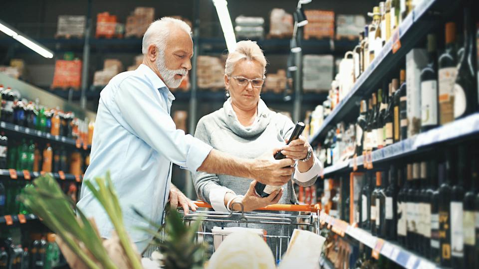 Closeup side view of early 60's couple walking through supermarket aisle and choosing some wine for tonight's dinner.