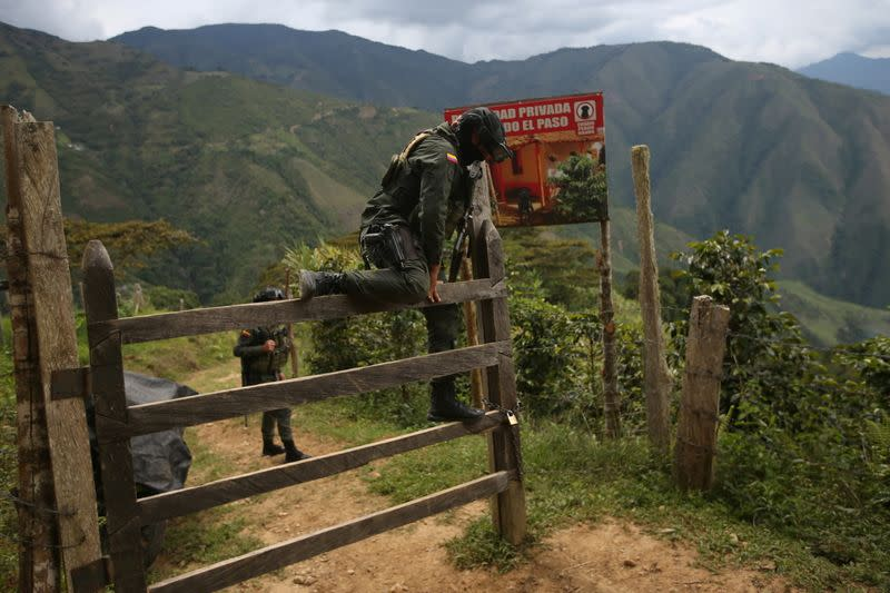A policeman climbs over a fence to access a road that leads to an illegal mine in Buritica