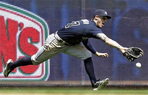 Atlanta Braves left fielder Jordan Schafer cannot come up with a ball hit by Milwaukee Brewers' Jean Segura during the fifth inning of a baseball game on Sunday, June 23, 2013, in Milwaukee. (AP Photo/Morry Gash)