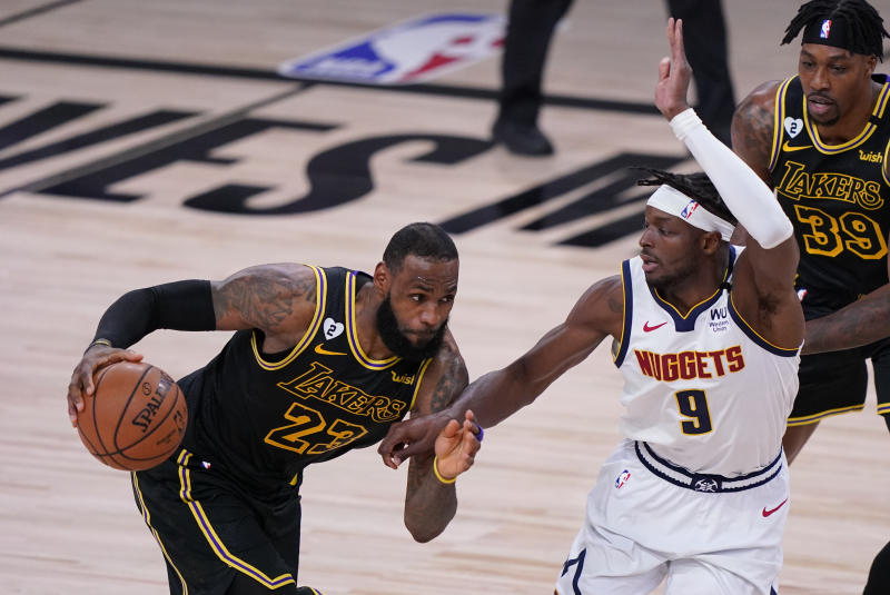 Los Angeles Lakers' LeBron James (23) drives past Denver Nuggets' Jerami Grant (9) during the second half of an NBA conference final playoff basketball game Sunday, Sept. 20, 2020, in Lake Buena Vista, Fla. (AP Photo/Mark J. Terrill)